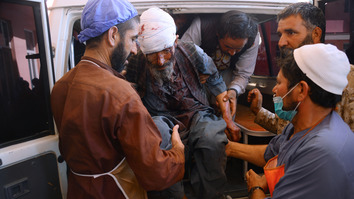 A wounded man is brought to a hospital in Herat after a roadside bomb hit a bus in Farah July 31. [Hoshang Hashimi/AFP]