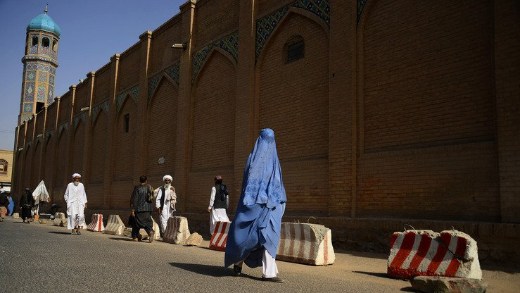 An Afghan woman wearing a burqa walks in front of Jama Mosque in Herat on July 15, 2018. [Hoshang Hashimi/AFP]