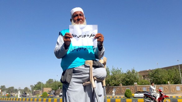 Ziauddin, 65, holds a sign that says 'No more war' in Pashtu before heading to Kabul August 7 in Herat city. He lost one of his legs in a roadside bombing in Herat. [Nasir Salehi]