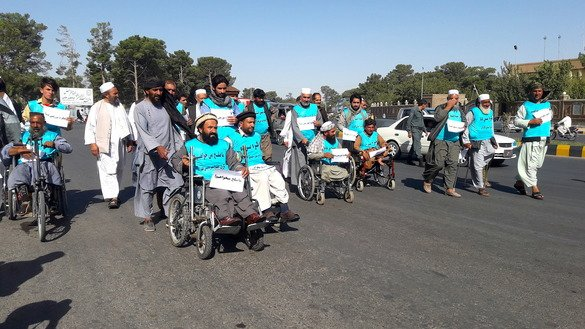 Twenty Afghan amputees, some in wheelchairs and others on crutches, can be seen August 7 in Herat city as they head to Kabul to spread a message of peace and demand that the Taliban end the bloodshed. [Nasir Salehi]