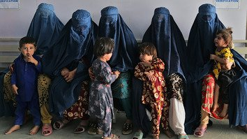 Afghan women wait during the visit of the United Nations High Commissioner for Refugees Filippo Grandi at the Azakhel Voluntary Repatriation Centre in Nowshera on September 8, 2018. [Abdul Majeed/AFP]