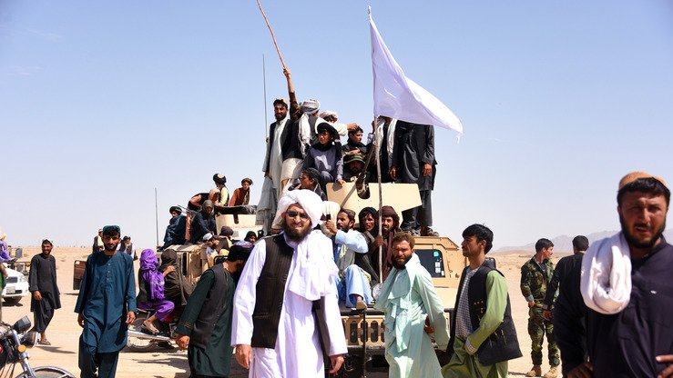 Taliban militants and residents stand on an Afghan army Humvee as they celebrate a nationwide ceasefire June 17, the third day of Eid, in Maiwand District, Kandahar Province. [Javed Tanveer/AFP]
