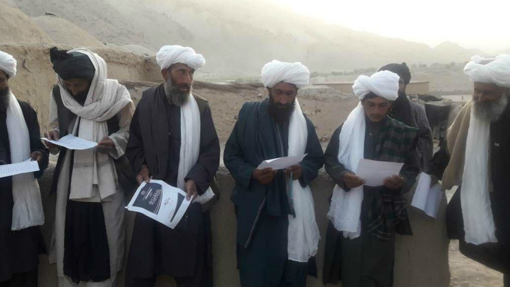 Taliban members are shown in August reading an Eid ul Adha flyer given to them by their leadership. Taliban leaders have been on the defensive in recent months trying to convince their own members and the Afghan people that they fight on behalf of Islam. [File]