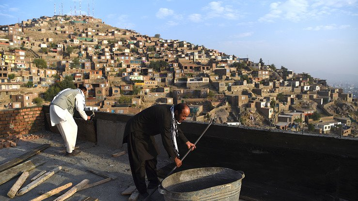 Men do construction work on their own roof in Kabul June 19. [Wakil Kohsar/AFP]
