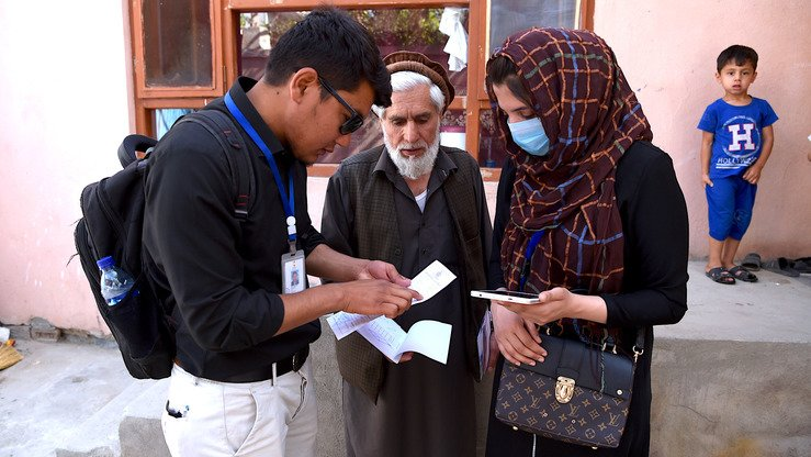 Afghan surveyors from the UN-Habitat team check documents during the registration of unregulated houses in Kabul June 12. [Wakil Kohsar/AFP]