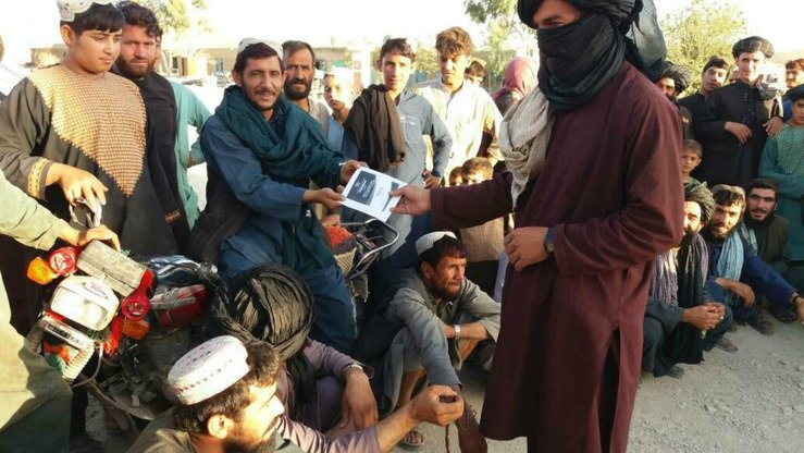 A Taliban member hands out a flyer to Afghans on Eid ul Adha. The Taliban often claim that most Afghans support them, so observers wonder why they fear democracy so much. [File]