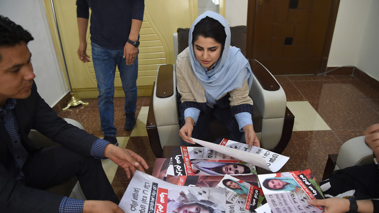 In this photo taken on September 26, an Afghan parliamentary election candidate checks her election campaign posters in Kabul. [Wakil Kohsar/AFP]