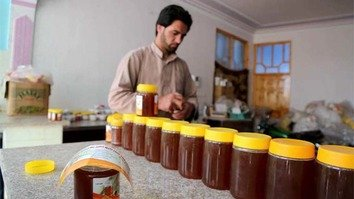 A worker packages honey in this undated photo as part of the Afghanistan Rural Enterprise Development Project in Ghaizan District, Herat Province. [Rumi Consultancy/World Bank]