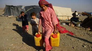 A drought-displaced Afghan girl August 3 carries water containers filled from a tanker at a camp for internally displaced persons in Injil District, Herat Province. The Taliban recently requested humanitarian aid for drought-affected areas under their control, but officials and analysts warn the request is merely a plot to fill the Taliban's coffers. [HOSHANG HASHIMI/AFP]