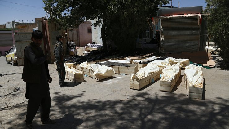 Ghazni residents August 14 stand next to coffins containing corpses on a roadside following clashes with Taliban fighters. The Taliban claims to want to help suffering Afghans, but in reality the group needs money to fund its destructive activities, analysts say. [ZAKERIA HASHIMI/AFP]