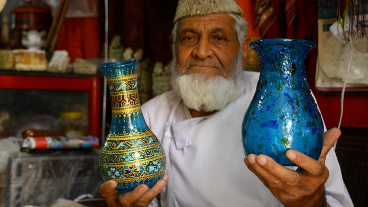 Sultan Ahmad Hamidi, 78, sells Herati glassware at his handicrafts shop in Herat Province August 2. [HOSHANG HASHIMI/AFP]