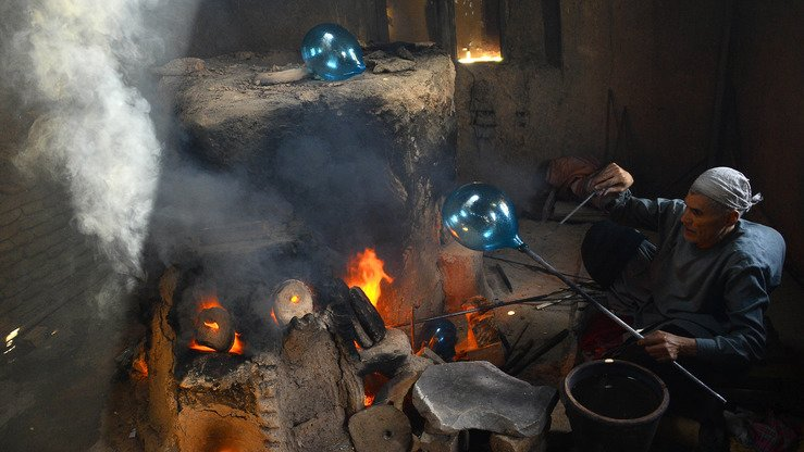 Glassblower Ghulam Sakhi is shown August 2 as he deftly blows and twirls molten glass into delicate blue and green goblets and vases -- a craft passed down for generations in Herat but now at risk of dying out. [HOSHANG HASHIMI/AFP]