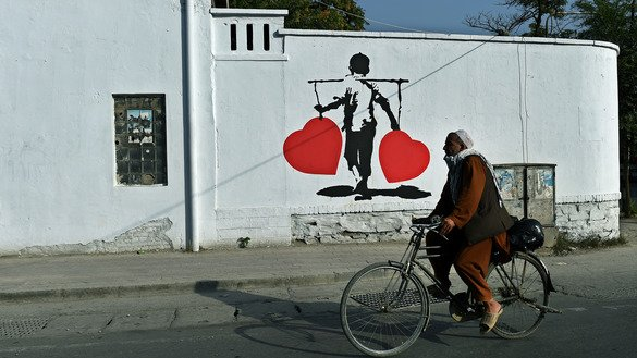A cyclist rides past an anti-corruption painting in Kabul July 24, 2015. [WAKIL KOHSAR/AFP]