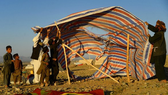 A group of Afghan men and children displaced by drought erect a tent at a camp for internally displaced persons in Injil District, Herat Province, August 5. [HOSHANG HASHIMI/AFP]