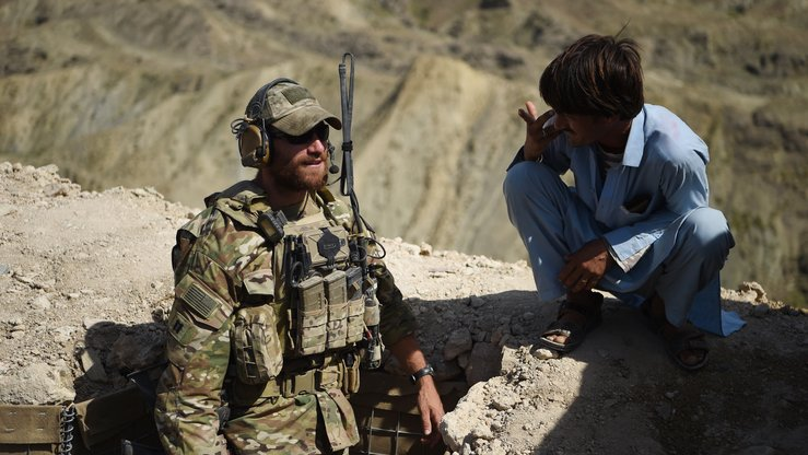 A US Army soldier from NATO and an Afghan Local Police officer guard a checkpoint during a patrol against ISIS militants in Deh Bala District, Nangarhar Province, on July 7. Rumours that the United States backs elements of ISIS are preposterous, Afghan officials and analysts say. [Wakil Kohsar/AFP]