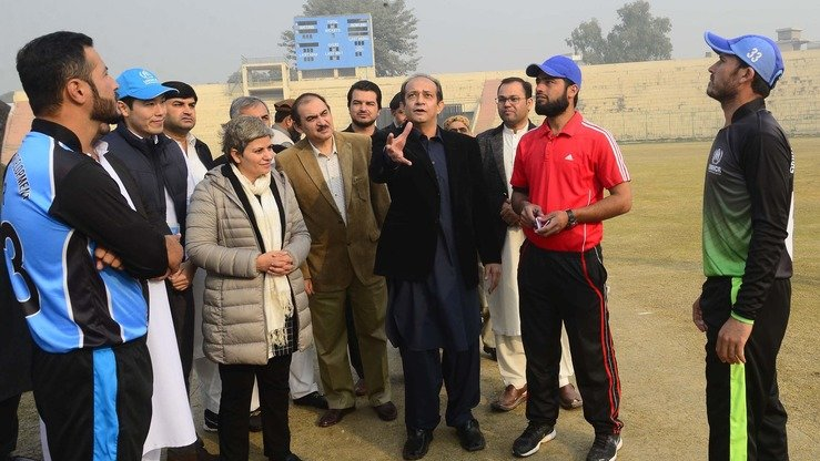 Commissioner for Afghan Refugees in KP Muhammad Abbas Khan takes part in a coin toss before the start of a cricket match in Peshawar December 5. [Shahbaz Butt]