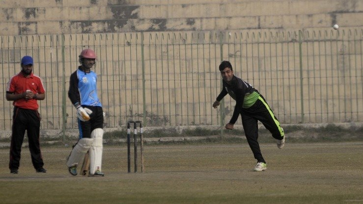 A player in the Afghan refugee league throws a ball in Peshawar December 5. [Shahbaz Butt]