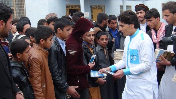 Idrees Syawash distributes educational books to schoolchildren December 10 in Mehtarlam, Laghman Province. [Khalid Zerai]