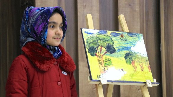 A girl from a school in Herat city stands by her painting at an event hosted by the Armanshahr/OPEN ASIA Foundation December 24. [Omar]
