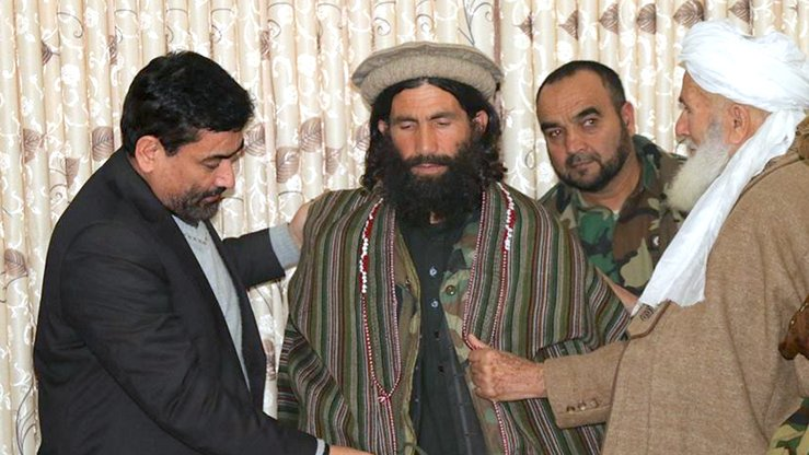 Badakhshan Governor Ahmad Faisal Begzad (left) puts a traditonal chapan on former Taliban commander Mawlawi Abdul Haq, who reconciled with the government and joined the peace process December 24 in Faizabad, Badakhshan Province. [Badakhshan governor's press office]