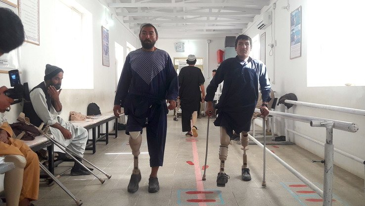 Recipients of prosthetic limbs walk in the hallway of the International Committee of the Red Cross (ICRC) centre in Helmand Province December 19. [Zia Samar]