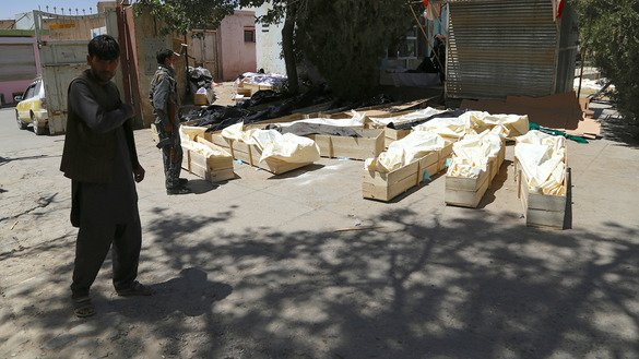 Afghans last August 14 stand next to coffins containing corpses on a roadside after a Taliban attack on Ghazni city. Afghan forces drove  Taliban fighters out of the stategic city of Ghazni August 15. [ZAKERIA HASHIMI/AFP]