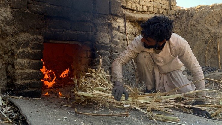 An Afghan worker at a Gora-making factory in Kama District adds more dried sugar canes to the oven as he produces Gora on December 26. [Khalid Zerai]