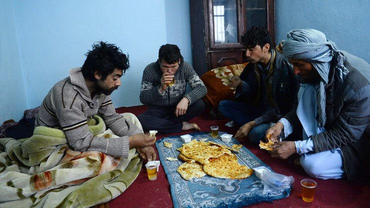 Afghan returnees eat breakfast January 3 at an International Organisation for Migration (IOM) transit centre in Herat Province after returning from Iran. [HOSHANG HASHIMI/AFP]