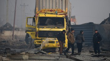 Afghan private security guards investigate at the site of a powerful truck bombing January 15, a day after it detonated near a foreign compound in Kabul. The Taliban claimed responsibility for the blast, which ripped through surrounding neighbourhoods, killing at least four Afghans and wounding more than 100. [WAKIL KOHSAR/AFP]