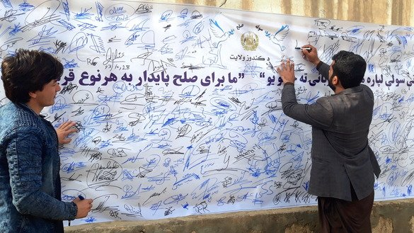 "A Kunduz resident signs a petition that reads ""We are ready to make any kind of sacrifice for lasting peace"" in Kunduz city January 23. [Hedayatullah]"