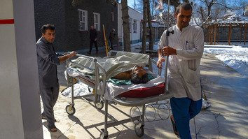 Afghan medics January 5 transport an injured man on a stretcher at Emergency Hospital in Kabul. [Wakil Kohsar/AFP]