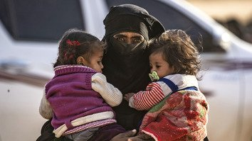 A fully veiled woman holds two little girls against her chest as hundreds of civilians, who streamed out of ISIS's last Syrian stronghold, walk towards a screening point for new arrivals run by US-backed Syrian Democratic Forces (SDF) outside Baghouz, Syria, March 5. [Delil Souleiman/AFP]