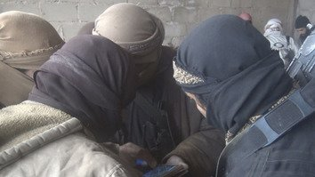 A photo published by ISIS on Telegram December 13 shows a group of its fighters huddling around a smartphone in Syria. [File]