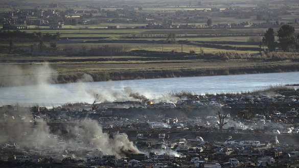 Smoke rises in ISIS's last remaining position on the eastern banks of the Euphrates River in the village of Baghouz on March 18, 2019. [Delil Souleiman/AFP]