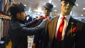 Ali Haidari, 18, dresses a mannequin as he waits for customers at his shop in Kabul February 18. Afghanistan's population -- estimated at 35 million -- is overwhelmingly young, with 63.7% under the age of 25. [Wakil Kohsar/AFP]