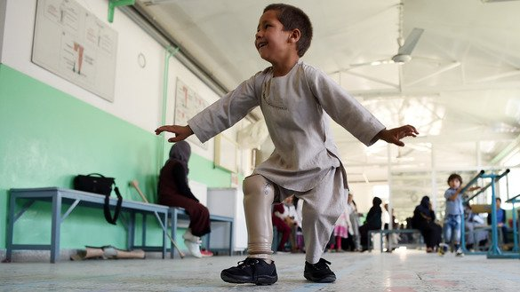 Ahmad Sayed Rahman, a five-year-old Afghan boy who lost his right leg when he was hit by a bullet in the crossfire of a battle, dances with his prosthetic leg at the International Committee of the Red Cross (ICRC) hospital for war victims and the disabled in Kabul on May 7. [Wakil Kohsar/AFP]