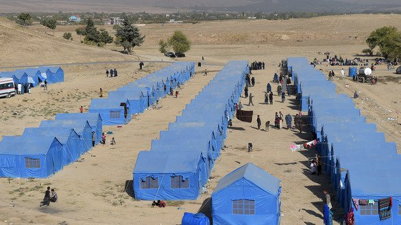 Afghans displaced by fighting in Kunduz between Afghan forces and Taliban insurgents walk at a makeshift camp in the outskirts of Kabul October 19, 2016. [Shah Marai/AFP]