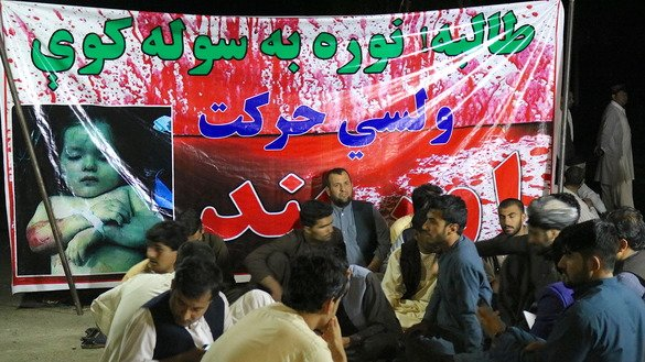 "Dozens of Helmand Province residents set up a tent in Lashkargah on March 24, 2018, a day after a car packed with explosives blew up outside a sports stadium in the city, killing at least 16 civilians and wounding 55. The banner reads, ""Taliban! You have to make peace -- the people's movement."" [Zia Samar]"