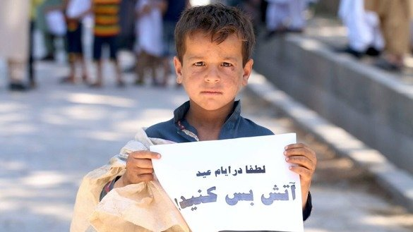 "A child holds a sign that reads ""Please make a ceasefire during Eid days"" in Herat city June 2. [Omar]"