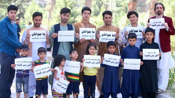 Afghan youth hold signs on June 2 in Herat city urging the Taliban to agree to a ceasefire. [Omar]