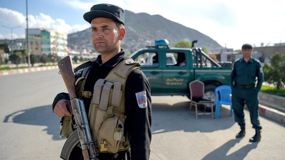An Afghan policeman looks on as passengers are stopped and searched at a checkpoint in Kabul April 30. [Wakil Kohsar/AFP]