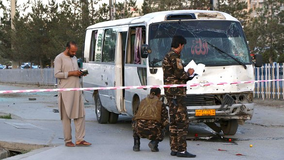 Afghan security personnel August 4 in Kabul investigate a bus that was carrying employees of Khurshid TV when a 'sticky bomb' exploded. [STR/AFP]